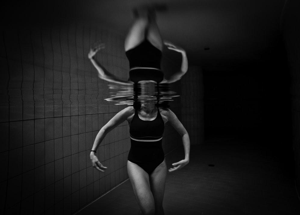 Jeune femme en maillot de bain pendant sa séance de rééducation en piscine