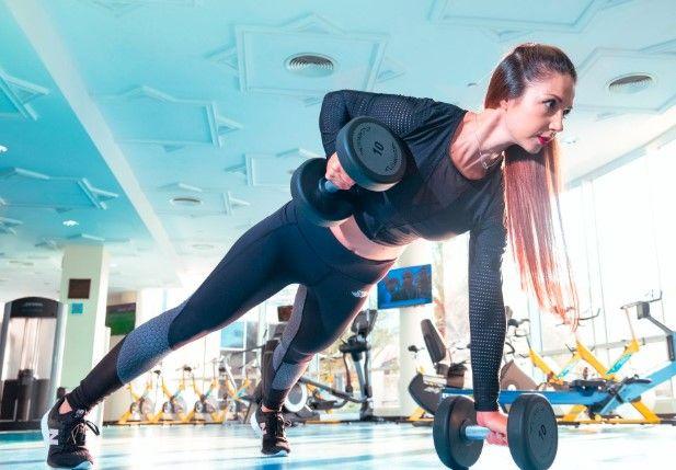 Jeune femme pendant un cours de body pump à la salle de sport