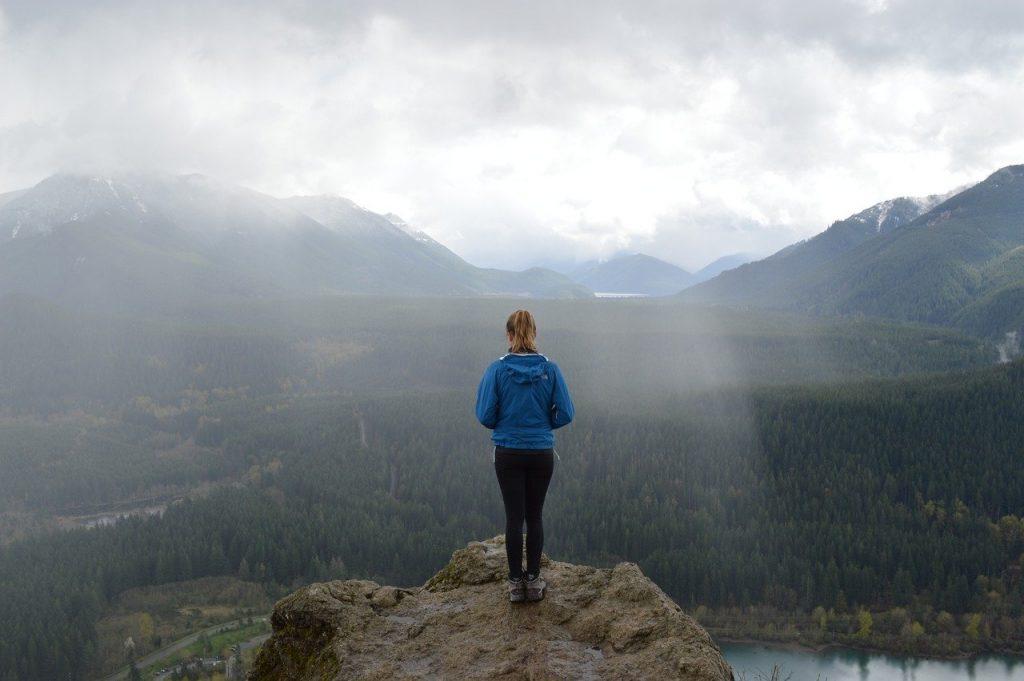 photo de dos d'une personne en haut d'un sommet